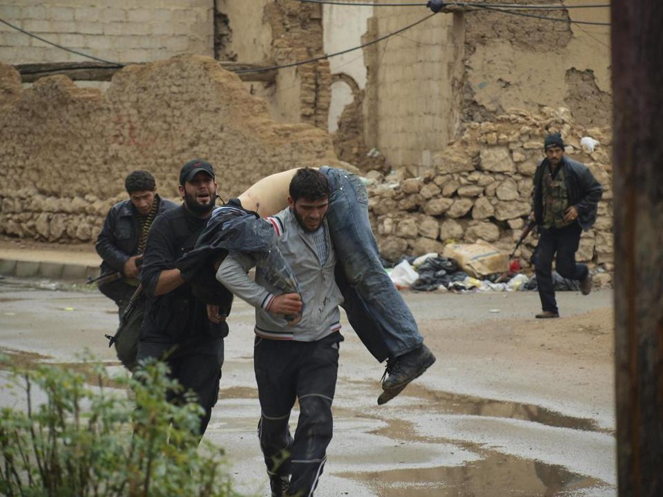 Members of the Free Syrian Army carried a man wounded during clashes at Daria with forces loyal to Syria's president.