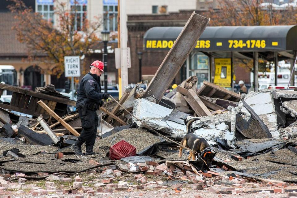 A State Police officer inspected the rubble with a canine after a natural gas explosion leveled Scores Gentleman's Club and damaged several nearby buildings on Worthington Street in Springfield.