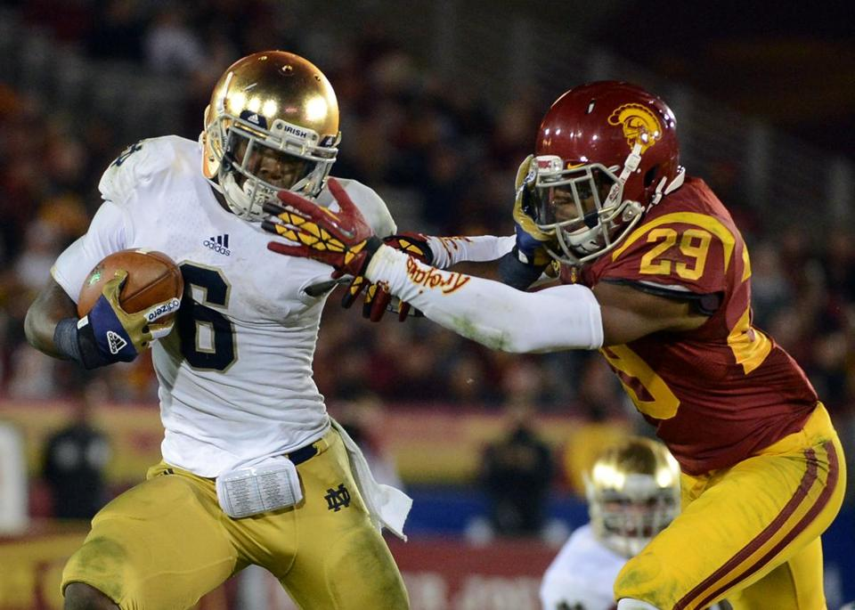 Notre Dame's Theo Riddick, who scored the only TD by the Fighting Irish, stiff-arms USC's Jawanza Starling.