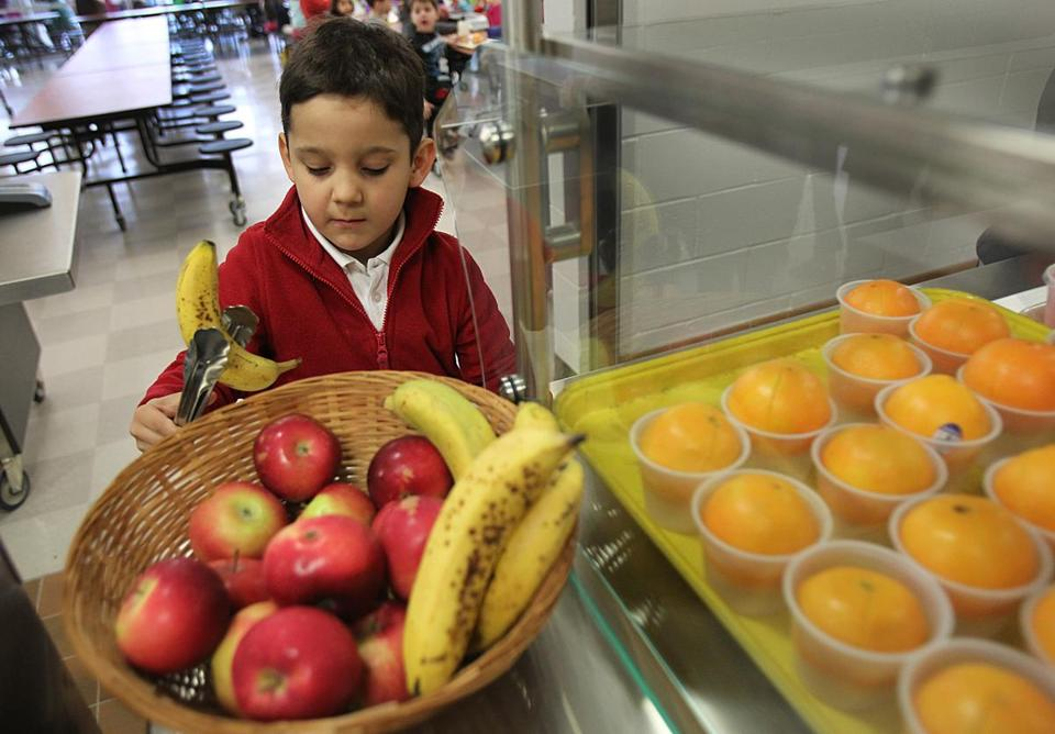 Lucas Lazos Munoz adds fruit to his lunch at the Runkle School in Brookline, where officials report fewer students buying meals this fall.