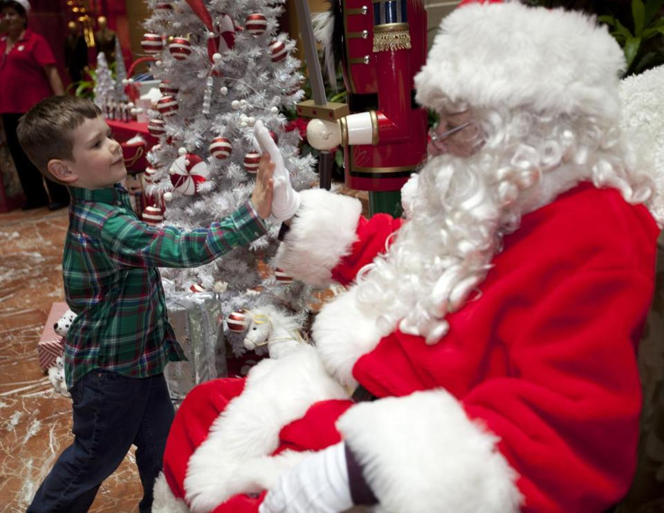 James Hazen, 4, of Boston shared a high five with Globe Santa at Copley Place last week.