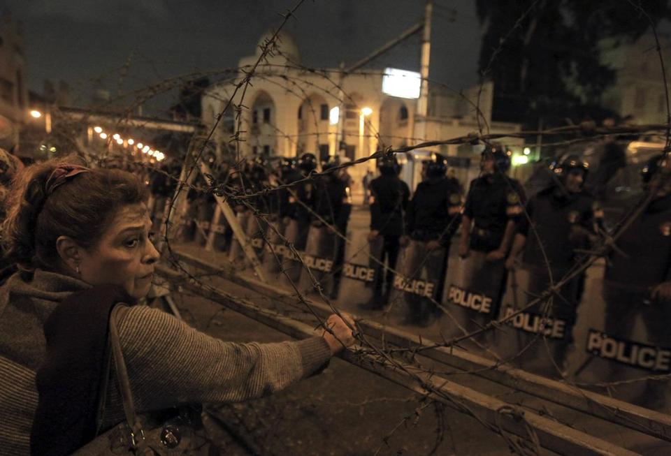 A woman stood near barbed wire in front of the presidential palace in Cairo.