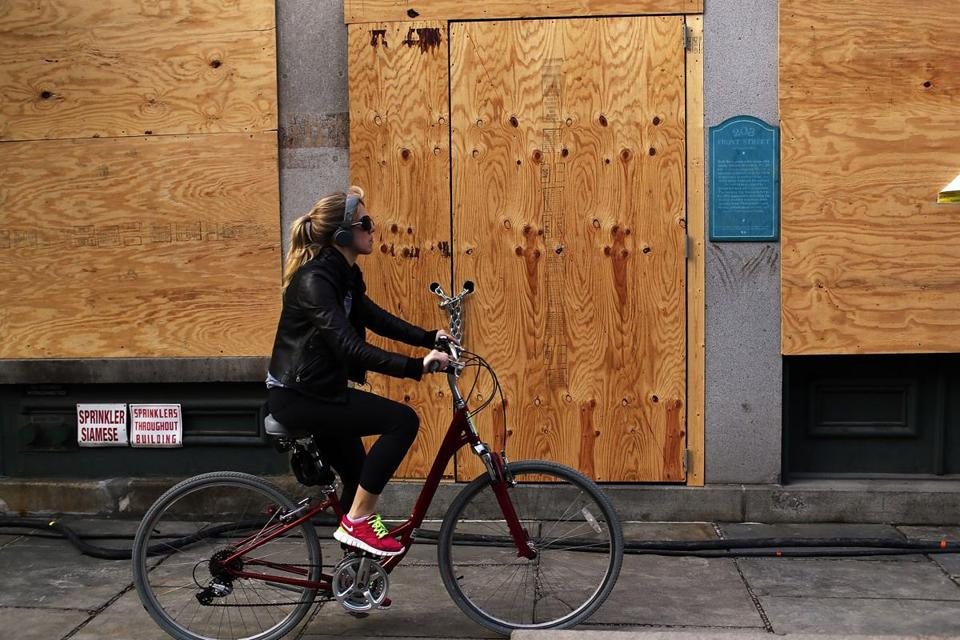 A woman on Monday rode by a business closed because of damage from Hurricane Sandy in the hard-hit South Street Seaport neighborhood in New York City.