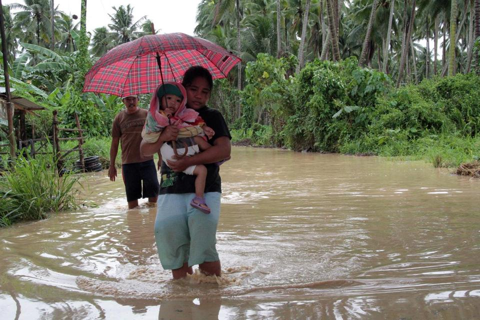 Filipinos navigated flooded roads Tuesday after a typhoon caused damage on the island of Mindanao.