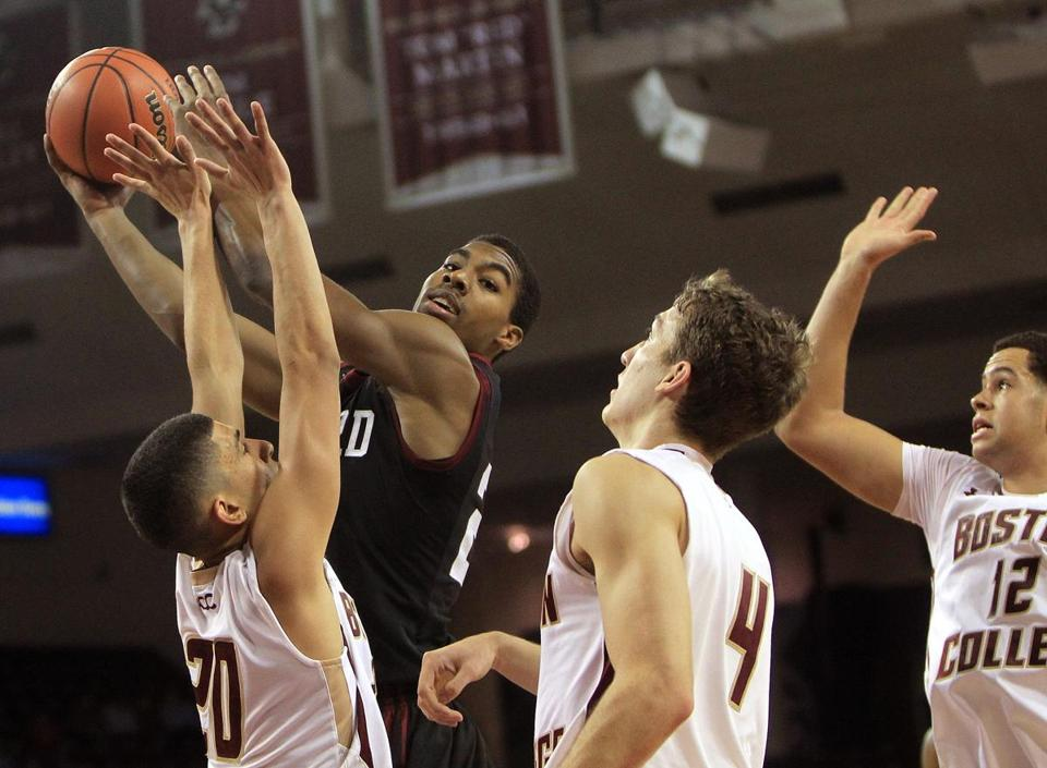 Harvard's Wesley Saunders looks for an open man after drawing Boston College defenders.
