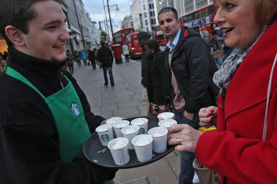 A Starbucks worker offered hot chocolate samples in London. The US company has more than 700 shops in Britain.
