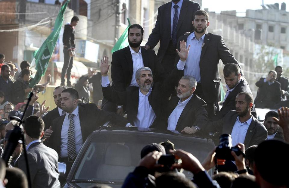 Hamas leader Khaled Meshaal (center) and Ismail Haniyeh (center right), the Hamas prime minister, waved from the roof of a vehicle following Meshaal's arrival in Rafah.