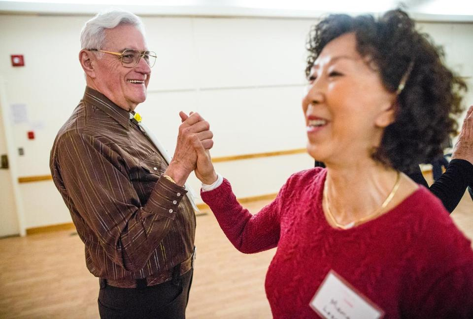 Eugene Saltsgaver (left) danced with new participant Maria Lesser  during a Fairs 'N Squares square dance club gathering at George Scott Hall in Framingham.