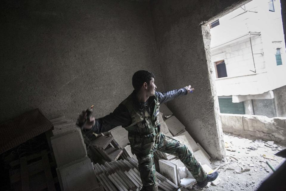 A rebel fighter threw a grenade toward Syrian troops loyal to President Bashar Assad during clashes in Aleppo, Syria.