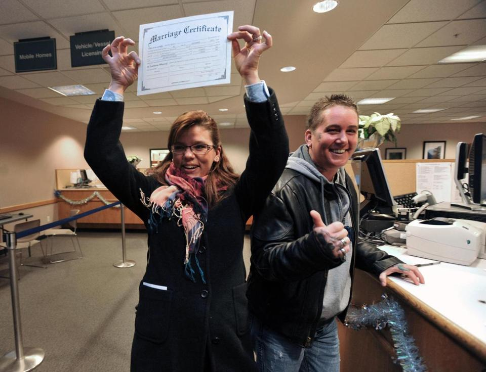 Sarah, left, and Melissa Adams show off the first same-sex marriage license approved at the Whatcom County Auditor's Office in Bellingham, Wash., on the first day the state's law legalizing gay marriage went into effect.