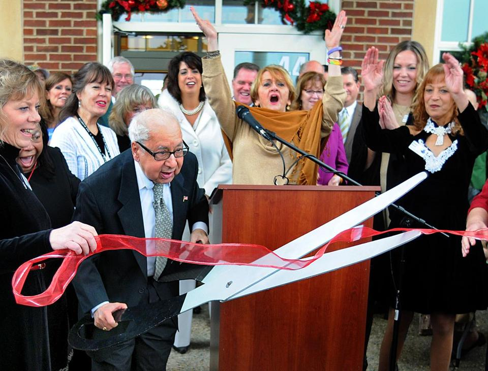 Chris Schembri cuts the ribbon at Plymouth's senior center, as Constance DiLego cheers at the podium.