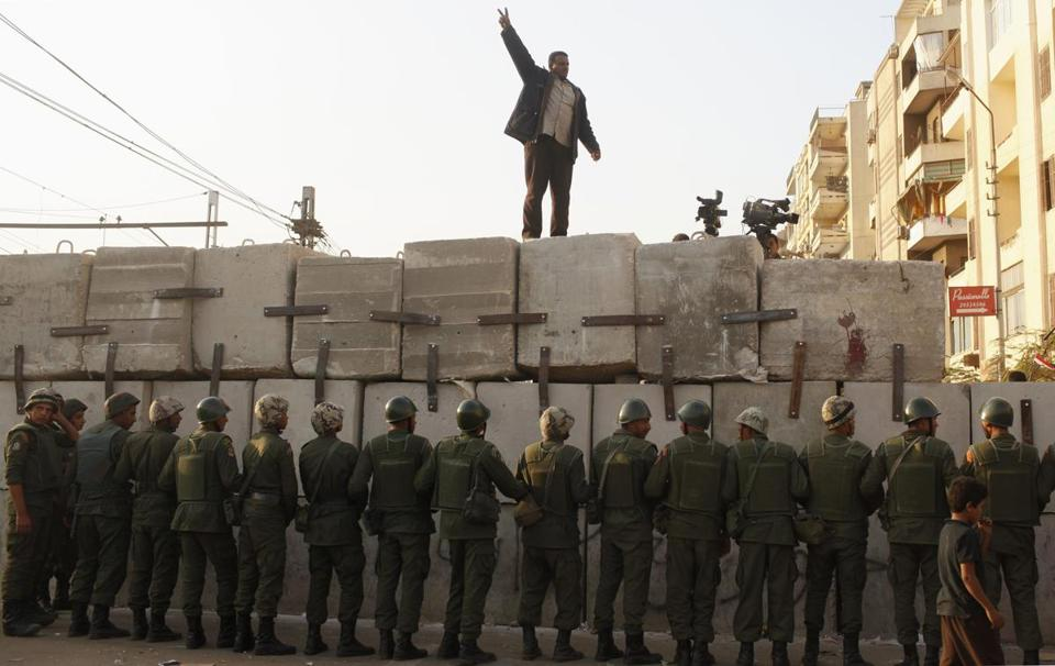 A demonstrator chanted slogans on a newly built barrier in front of soldiers guarding the presidential palace in Cairo.
