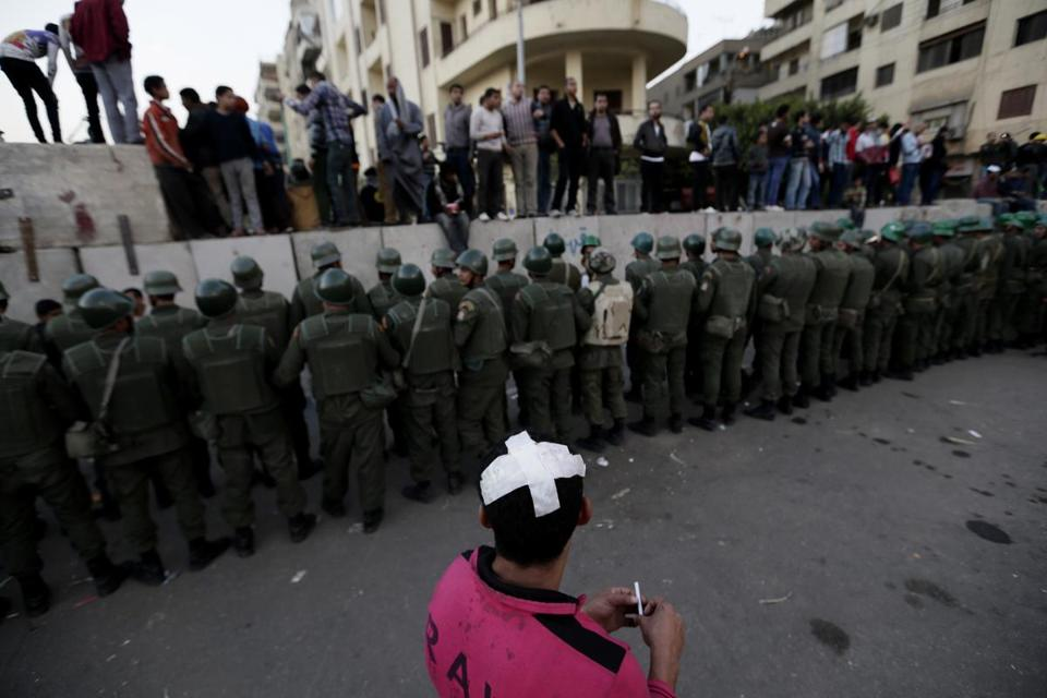 Egyptian army soldiers stood guard near the presidential palace in Cairo on Sunday as protesters stood on top of cement blocks. Monday was relatively quiet in the city, but both sides planned to hold demonstrations on Tuesday.