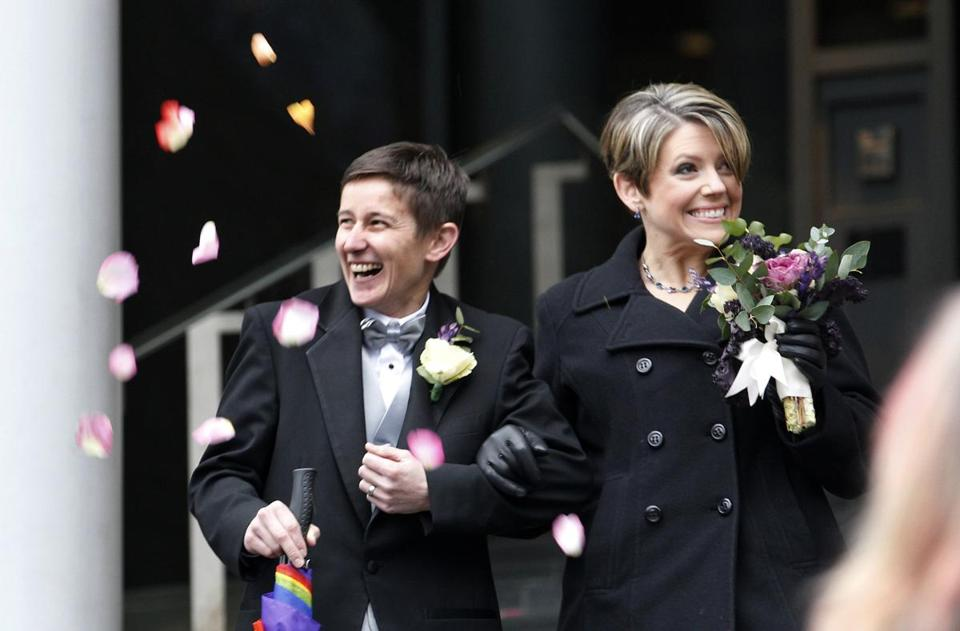 Newlyweds Heather Laird (left) and Dawn Rains were showered with flower petals as they left Seattle City Hall Sunday.