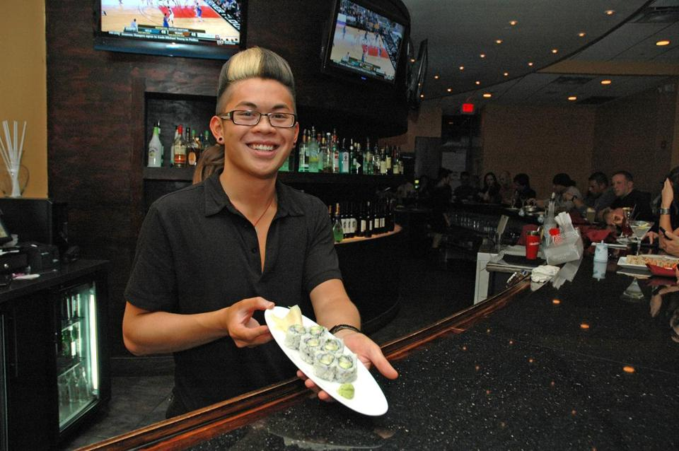 A waiter shows a tray of California roll at the bar.