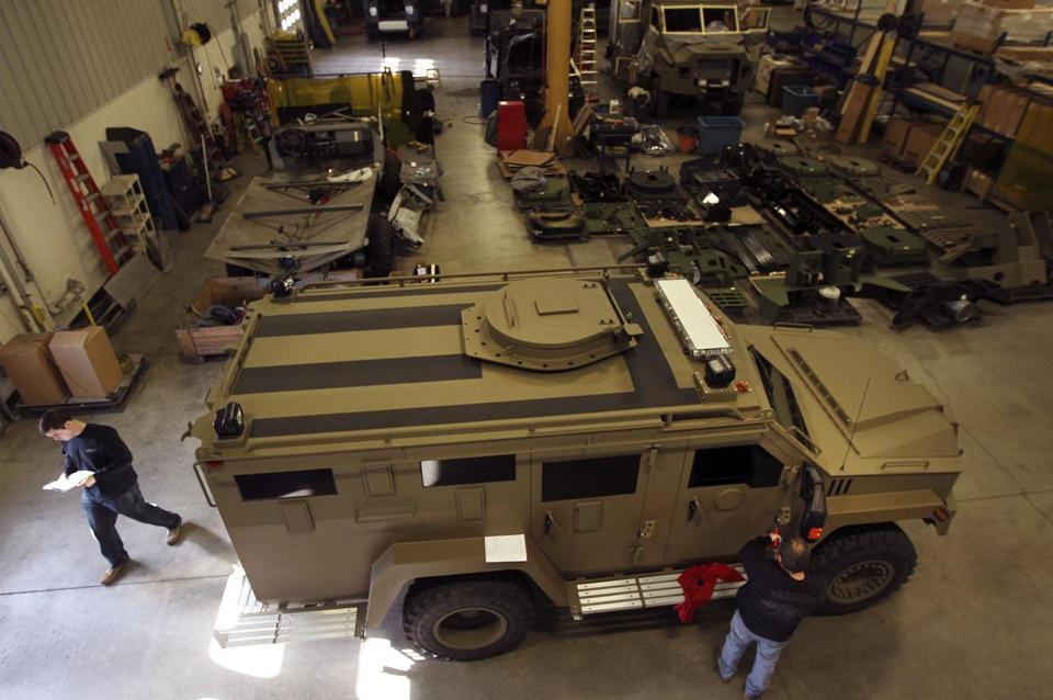 Employees at Lenco, an armored car manufacturer, work on SWAT trucks, popular with police departments, at its plant in Pittsfield.