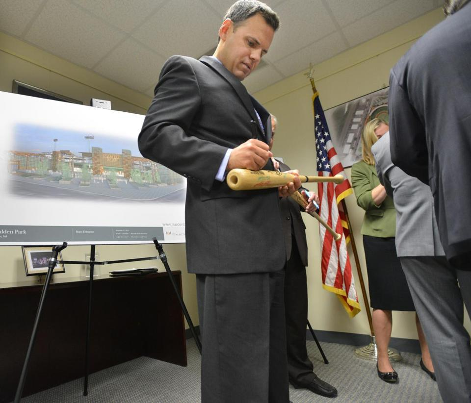 Mayor Gary Christenson signs a bat at a press conference on the agreement to build a minor league ballpark.