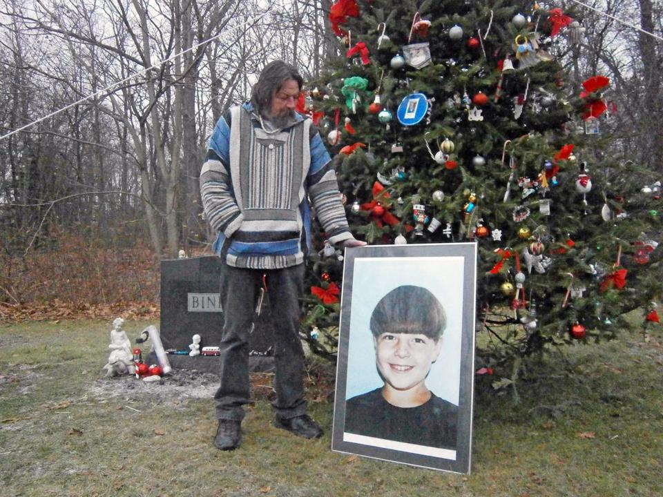Paul Binkley of Weymouth stands at the memorial Christmas tree with a picture of his son, Christopher.