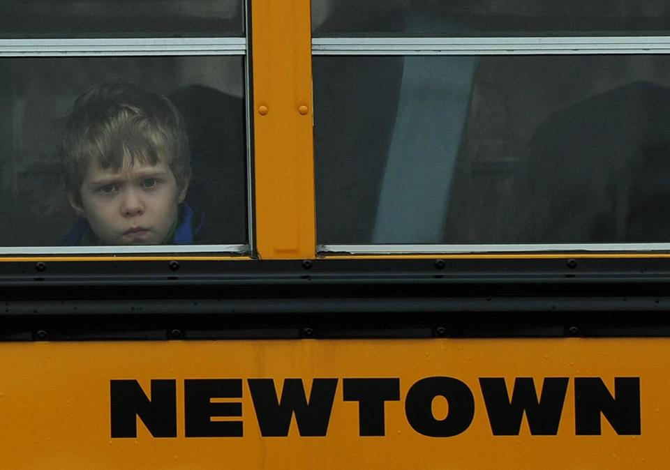 A child looked out of a bus window as it passed by Saint Rose of Lima Church, where the funeral of James Mattioli, 6, was taking place on Tuesday.