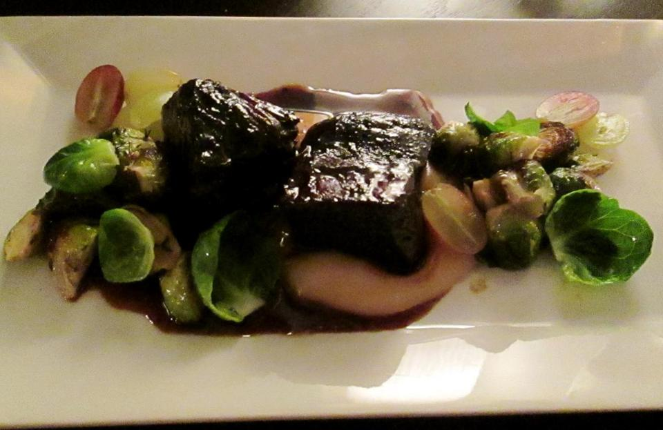 Boneless braised short ribs with grapes and roasted Brussels sprouts in a parsnip puree.