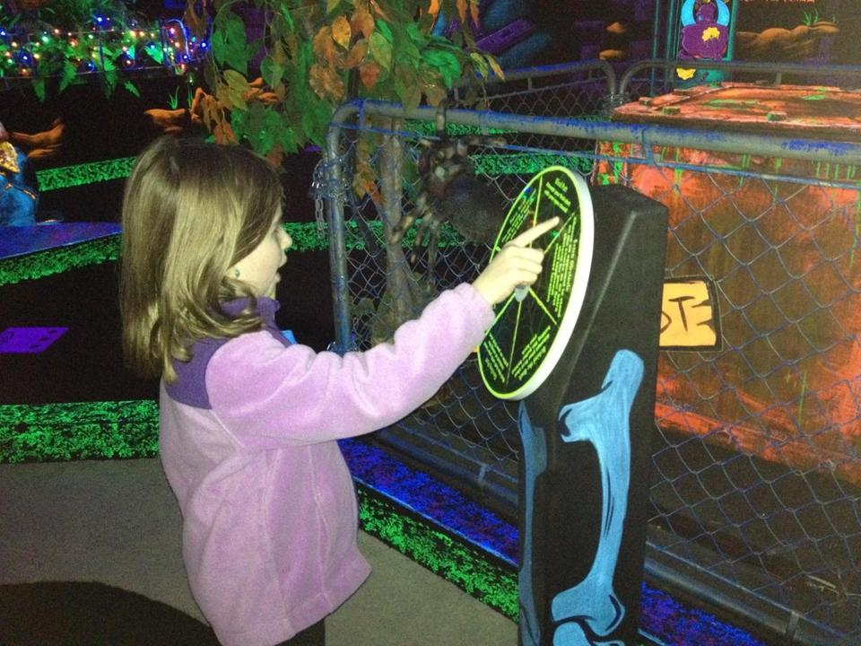 Ava, 8, at glow-in-the-dark mini golf at Monster Mini Golf in Norwood.