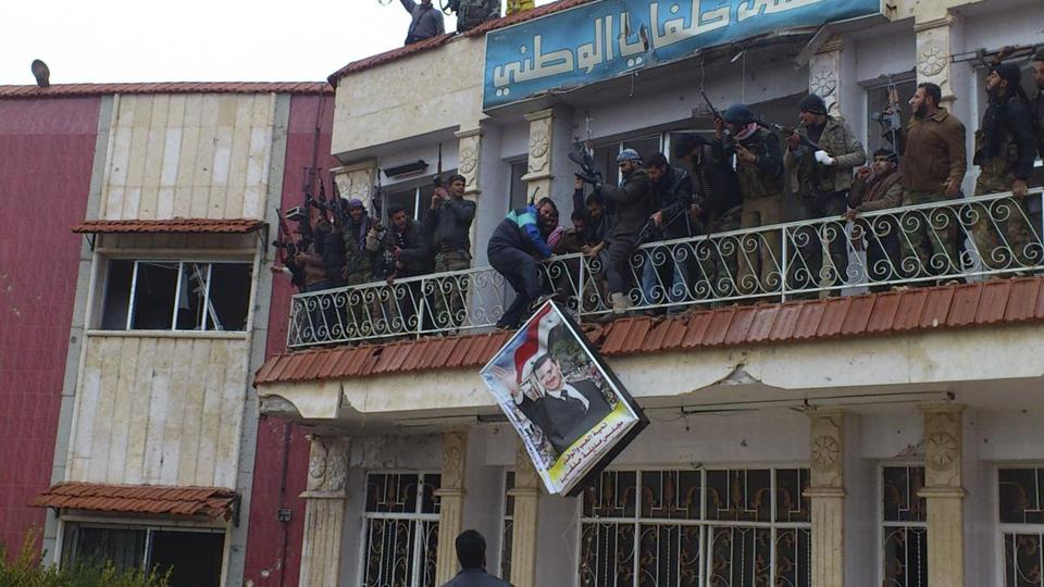 Rebels tossed a poster of President Bashar Assad from a hospital in Syria Tuesday after a battle with government troops.