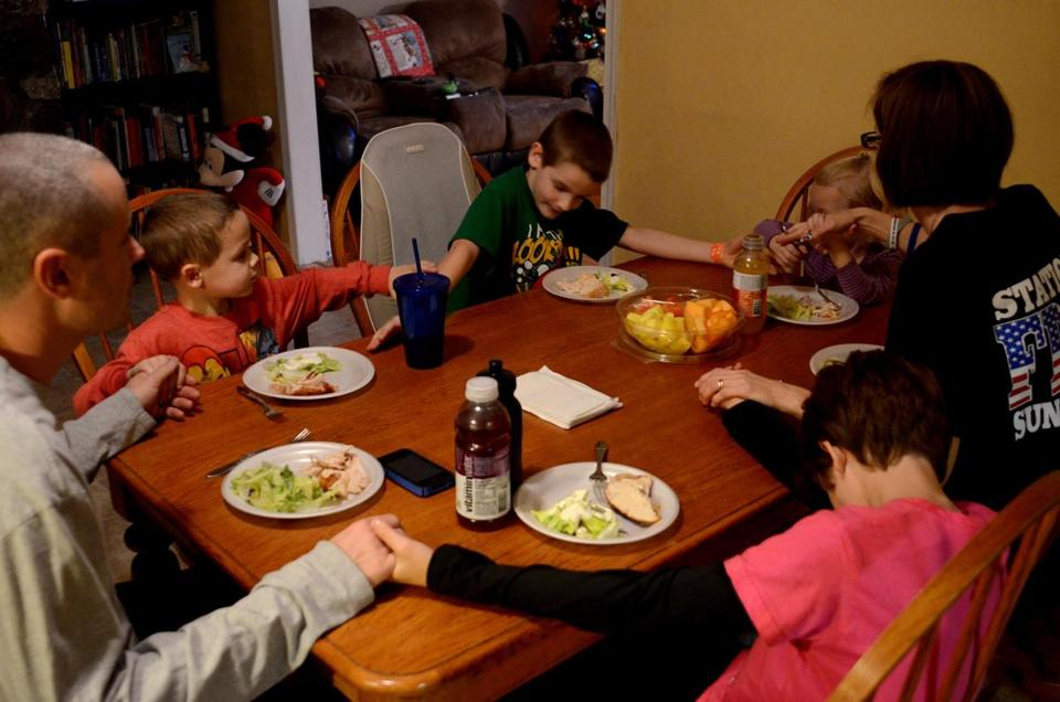 Nathan Norman (left), 5, prayed with his family at dinner as he prepared to meet with some special holiday guest Thursday.