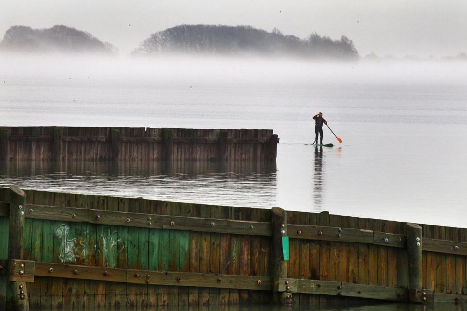 Colin Clark of South Boston paddles past the L Street Bathhouse after his journey toward the fog bank and Thompson Island, Dec. 18, 2012.