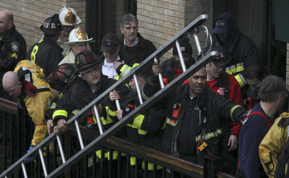 Boston rescue workers removed a rescue ladder after using it to help save a woman who was in the Fort Point Channel on Friday. The woman was not identified.