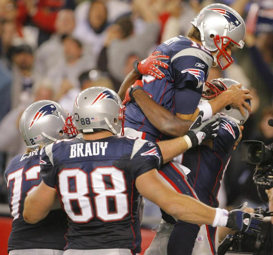 Tom Brady leaped into Randy Moss' arms after the receiver caught his second touchdown.