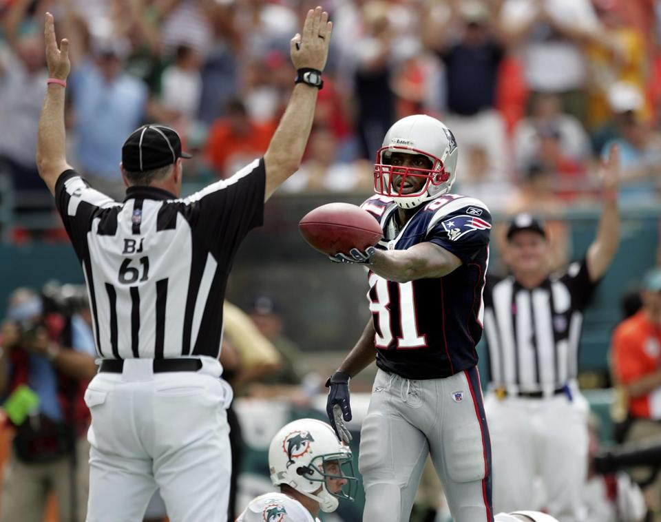 Randy Moss handed off the ball after scoring one of his two touchdowns against the Dolphins.