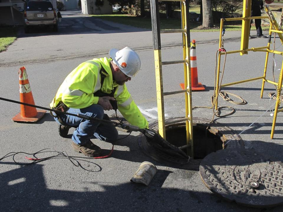 National Grid worker Bob Witney helps feed a new power cable into a manhole on Mag­nolia Avenue in Gloucester as part of an ongoing upgrade to Cape Ann's infrastructure.
