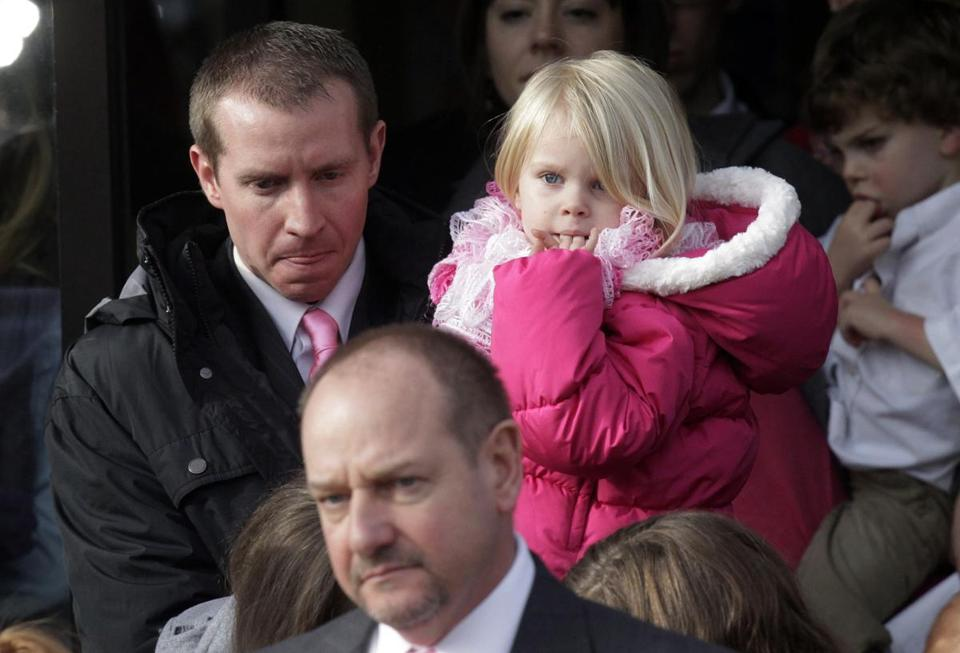 Robbie Parker carried his daughter, Madeline, 4, following funeral services for his 6-year old daughter Emilie Parker, a victim in the Newtown shootings.