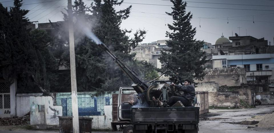 A Free Syrian Army fighter fired an anti-aircraft weapon during an air strike in Binsh near Idlib on Sunday.