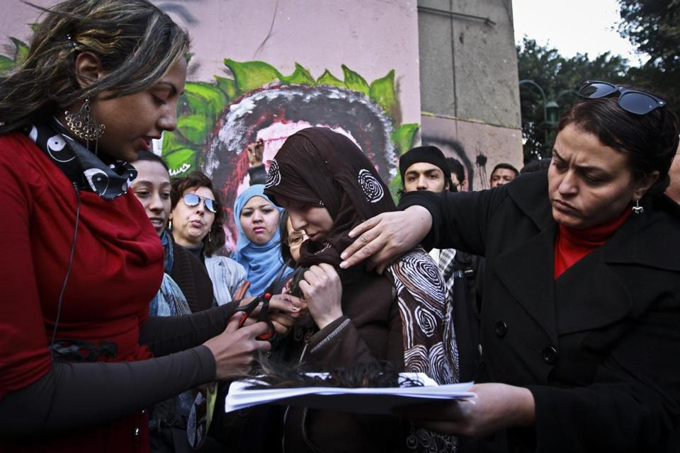 A woman cut another woman's hair during a Cairo demonstration in protest of the Islamist-oriented constitution.