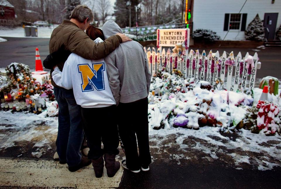 Members of the Rutter family of Sandy Hook, Conn., embraced early Christmas morning as they stood near memorials to those who died at the Newtown massacre.