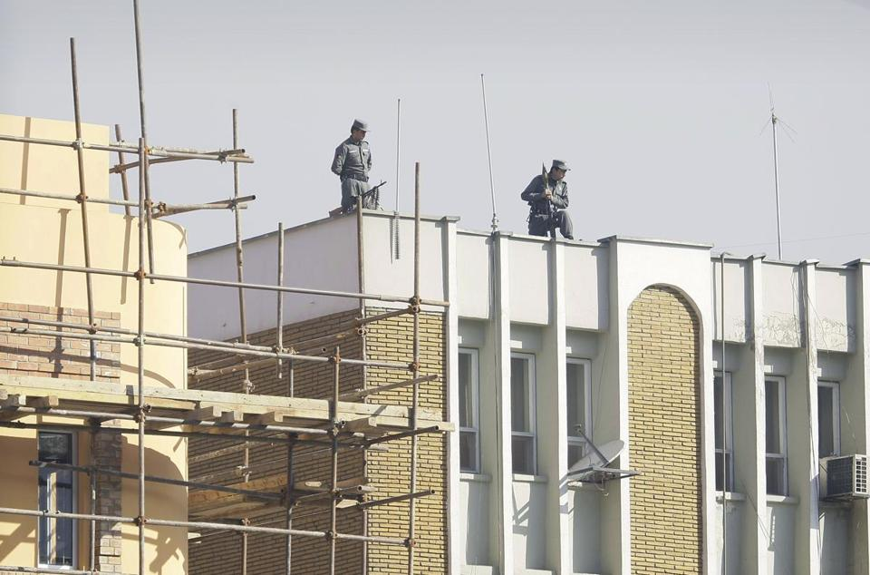 Afghan policemen watched from top of the Kabul police headquarters following the killing of an American adviser.