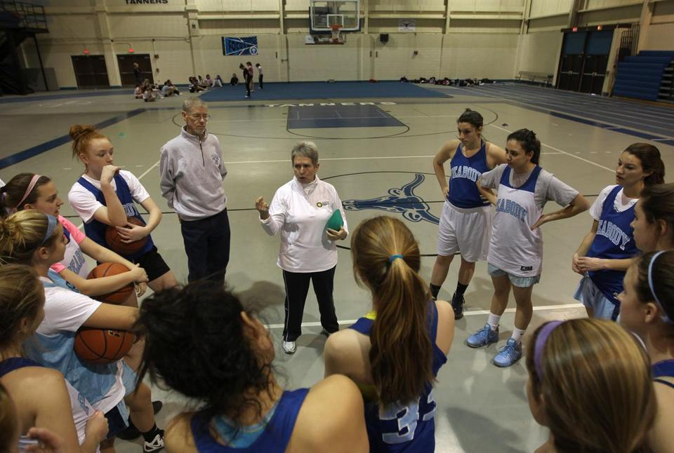 Peabody girls' basketball coach Jane Heil, center, spoke Wednesday to her team and husband and volunteer assistant coach Bob Heil, left.