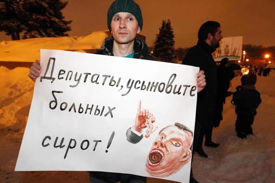 "A man holds a poster saying ""Lawmakers, adopt ill orphants"" as he protests against a bill banning adoption of Russian orphans by American citizens in St. Petersburg, Russia."