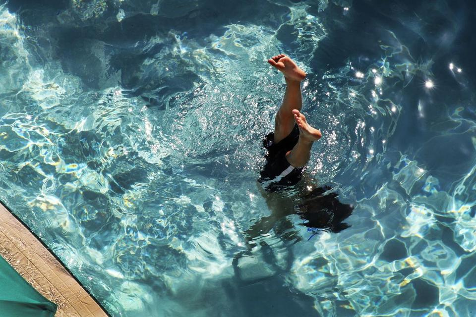 Alex King, 11, of Chicago walks on his hands in a swimming pool in Hollywood, Fla.