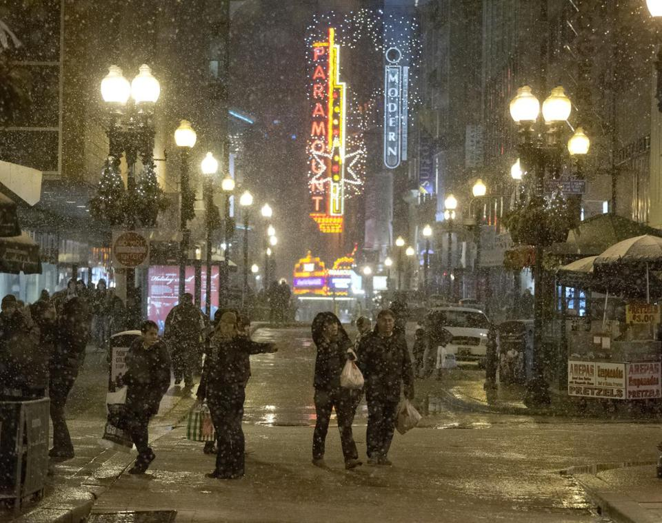 Shoppers in Downtown Crossing frolicked in the snow that fell Saturday evening. The region may see up to a foot.