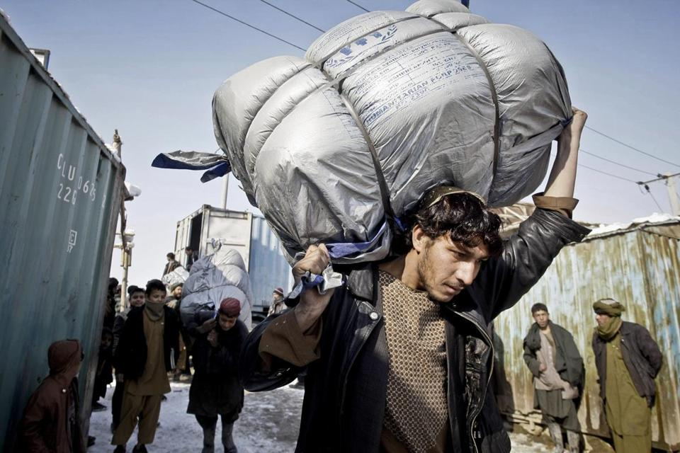 Afghan refugees carried sacks of donated blankets Sunday from the UN relief agency at a camp in Kabul.