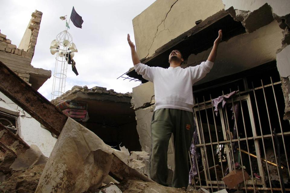 A man mourned amid debris after a car bomb attack Monday in Hillah, south of Baghdad.