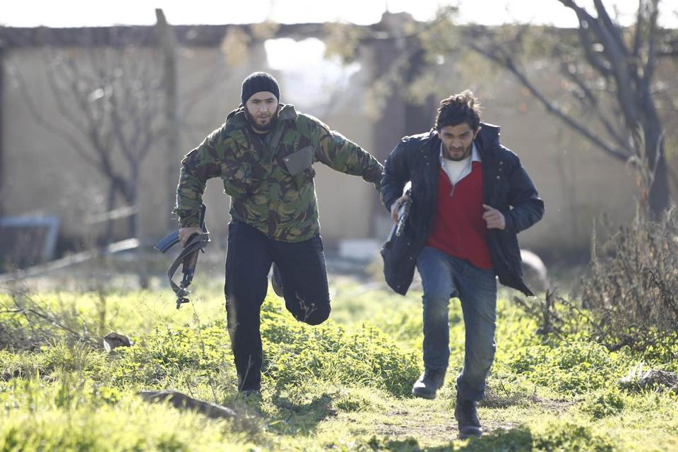 Free Syrian Army fighters ran for cover at the front line near Menagh military airport in north Aleppo on Monday.