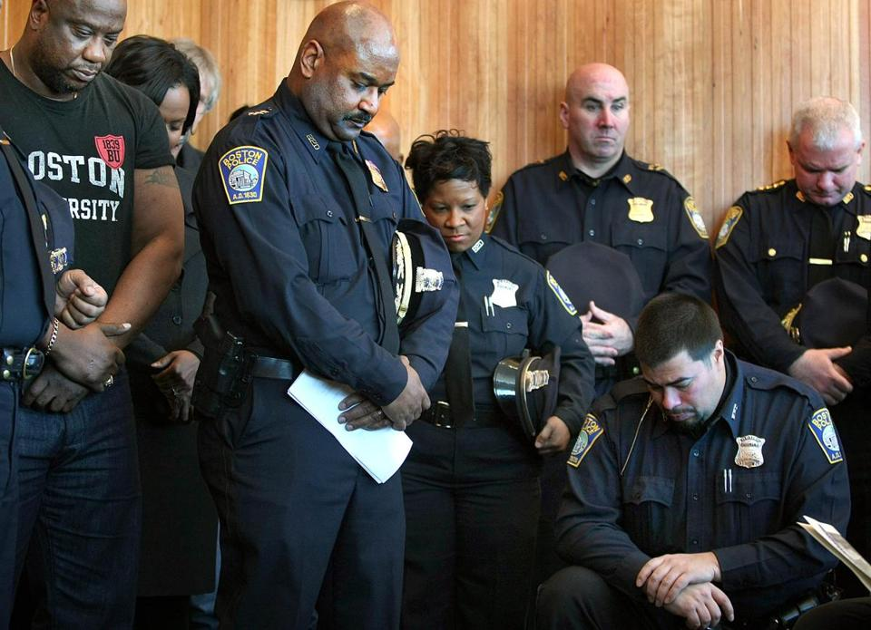 Police officers bowed their heads during a prayer after the ceremony naming a room in the Dudley Square station for Sergeant Horatio J. Homer, the city's first black officer.