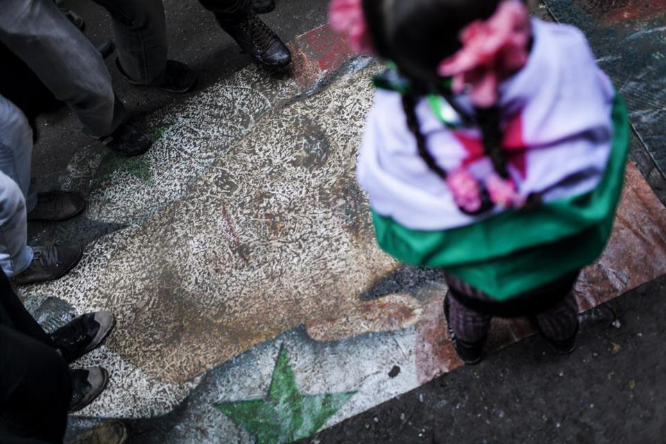 Syrians stomped on a portrait of President Bashar Assad during a protest in Aleppo on Friday. The UN said more than 60,000 people have been killed since the crisis began.
