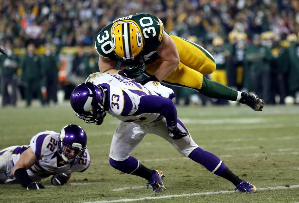 John Kuhn of the Packers flies over Minnesota's Jamarca Sanford to score on a 9- yard TD reception during the first half of his team's wild-card victory.