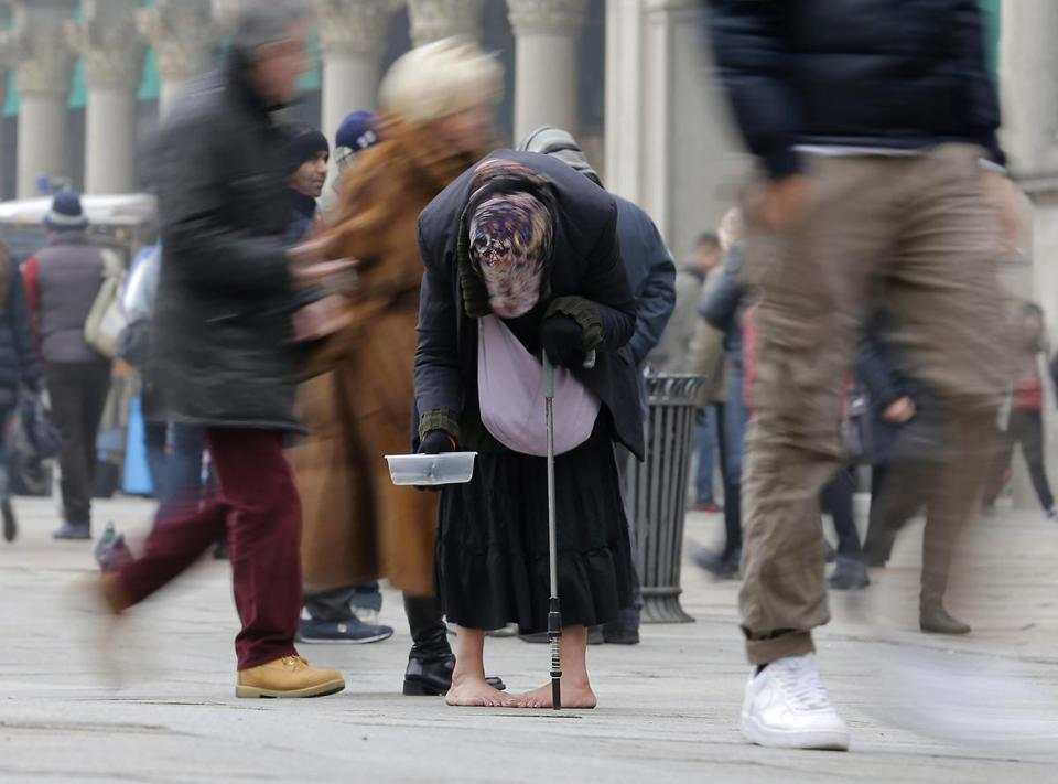 A woman pleaded for money in Milan on Tuesday. Many economists expect the eurozone to remain in a recession through winter, with unemployment possibly hitting 12.4 percent.