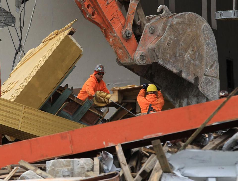 Workers prepared to remove an angel from St. Joseph Church in Salem as demolition began Friday.