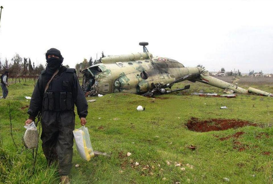 A Syrian rebel carried food as he walked in front of a damaged helicopter at Taftanaz air base, overtaken by rebels in Idlib Province in northern Syria.